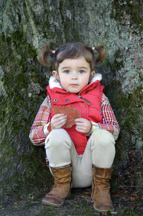 Petite fille adorable assise contre un arbre photos stock