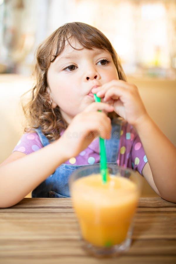 Petite fille adorable buvant du jus d'orange à la maison photo libre de droits