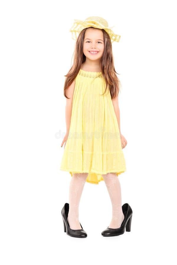 Petite fille adorable dans la robe et le chapeau jaunes de fantaisie photo libre de droits