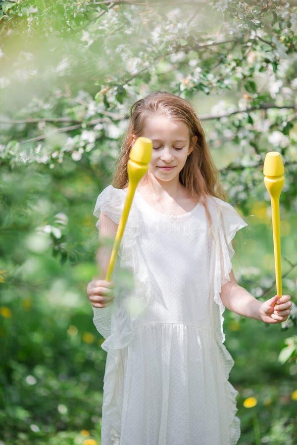 Petite fille adorable dans le jardin de floraison de pomme la belle journée de printemps photos stock