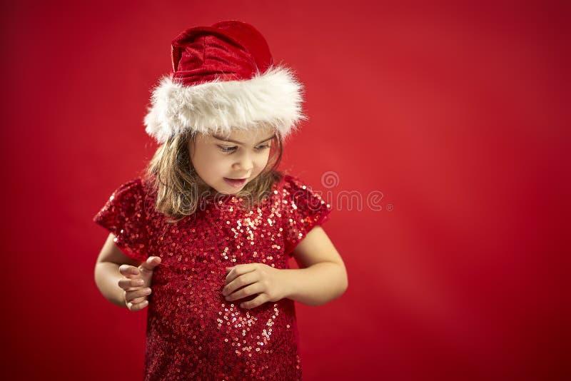 Petite fille adorable dans une robe de Noël dans le chapeau d'une Santa image libre de droits