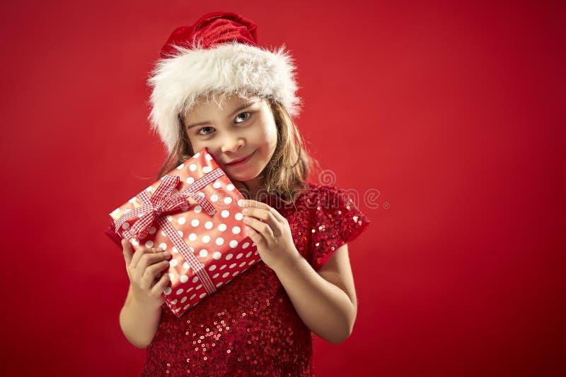 Petite fille adorable dans une robe de Noël dans le chapeau d'une Santa avec un cadeau de Noël images stock