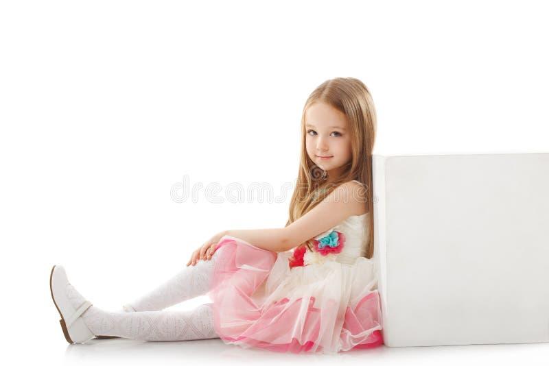 Petite fille adorable posant le penchement sur le cube images libres de droits