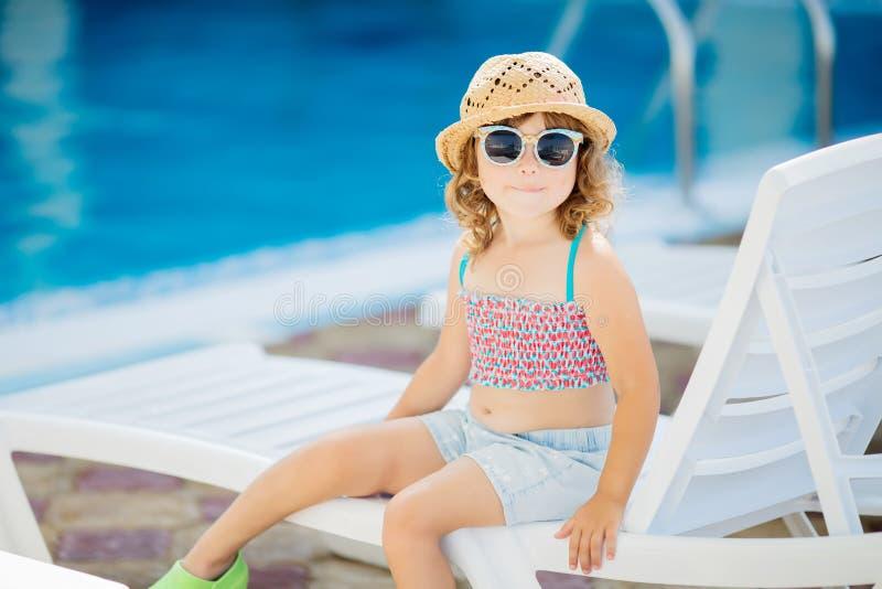 Petite fille adorable s'asseyant près de la piscine photo stock