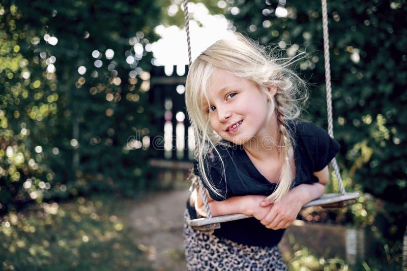 Petite fille adorable souriant tout en jouant sur une oscillation d'arbre photographie stock libre de droits