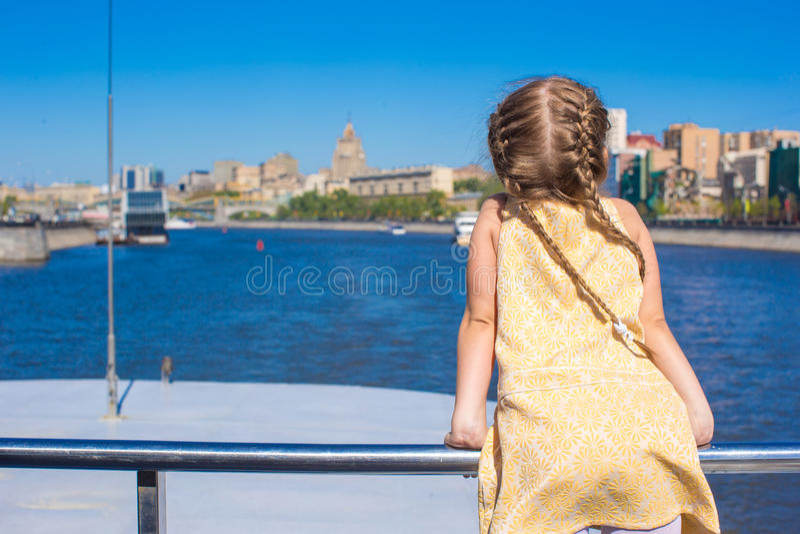 Petite fille adorable sur la plate-forme d'une navigation de bateau dans la grande ville photos libres de droits