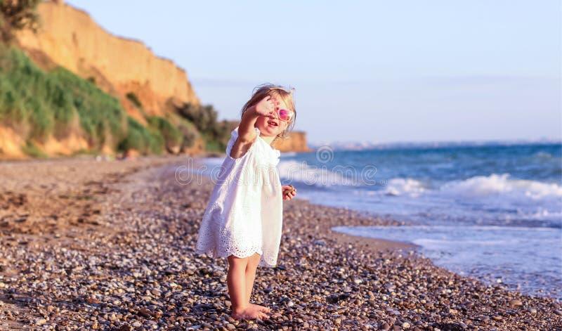 Petite fille adorable sur une plage près d'une mer image libre de droits