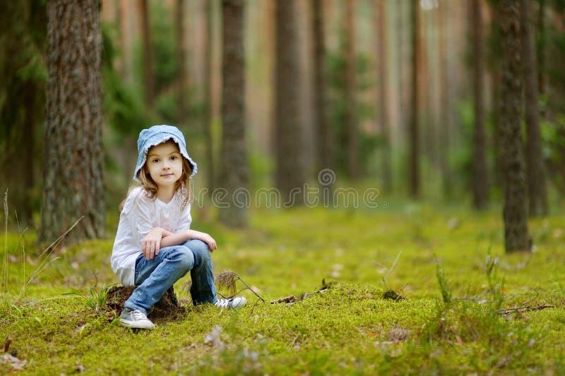 Petite fille adorable trimardant dans la forêt photo stock