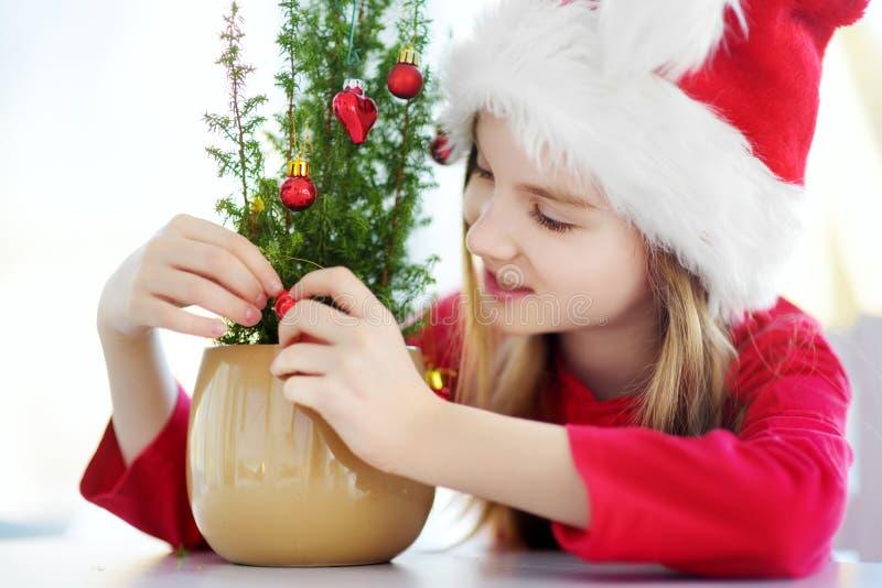 Petite fille adorable utilisant le chapeau de Santa décorant le petit arbre de Noël dans un pot le matin de Noël images stock