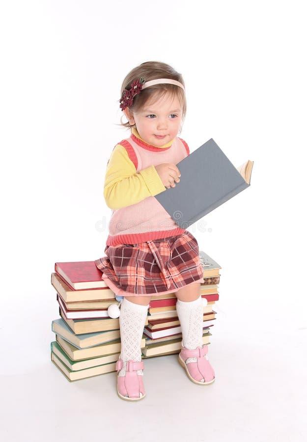 Petite fille affichant pensivement un livre photo stock