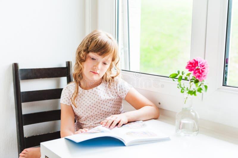 Petite fille affichant un livre photographie stock