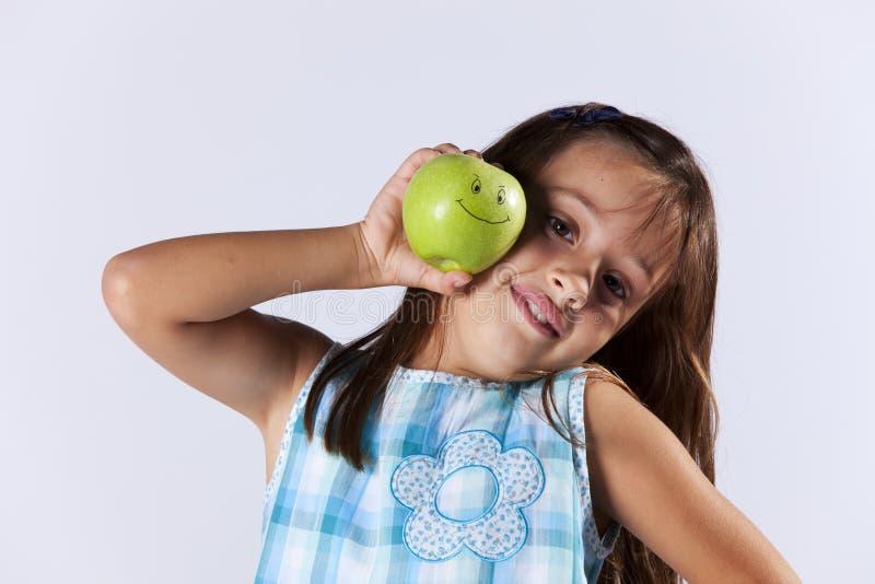 Petite fille affichant une pomme verte images libres de droits