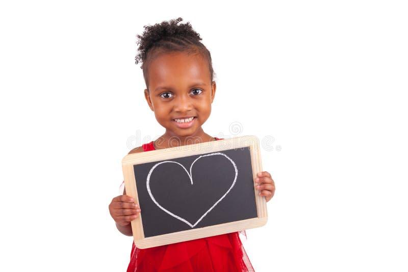Petite fille africaine adorable avec l'ardoise image libre de droits