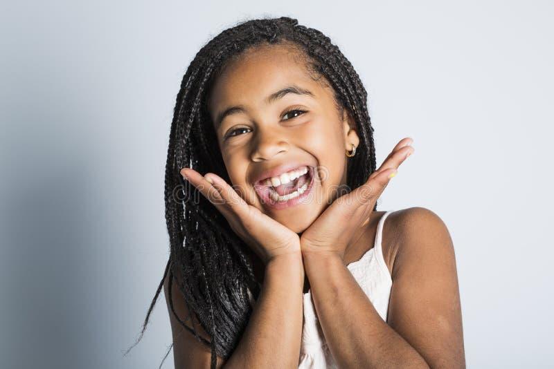 Petite fille africaine adorable sur le fond de gris de studio photos stock
