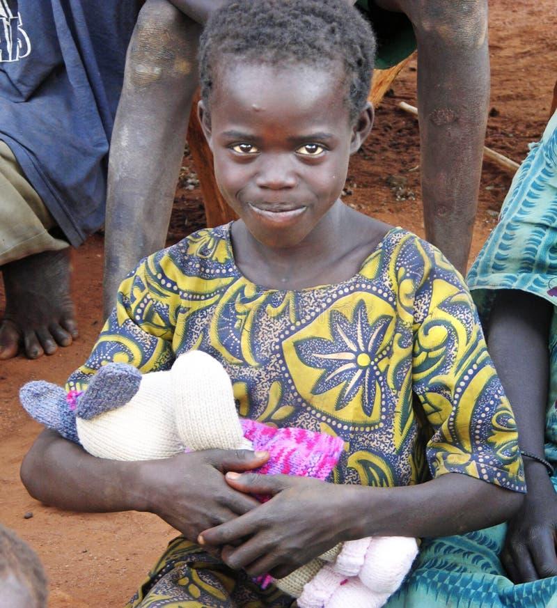 Petite fille africaine douce comblée avec le premier jouet mou photos stock