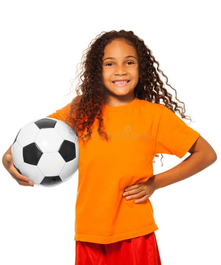 Petite fille africaine jugeant le ballon de football d'isolement photographie stock libre de droits