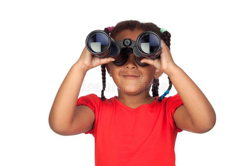 Petite fille africaine regardant par des jumelles photos stock
