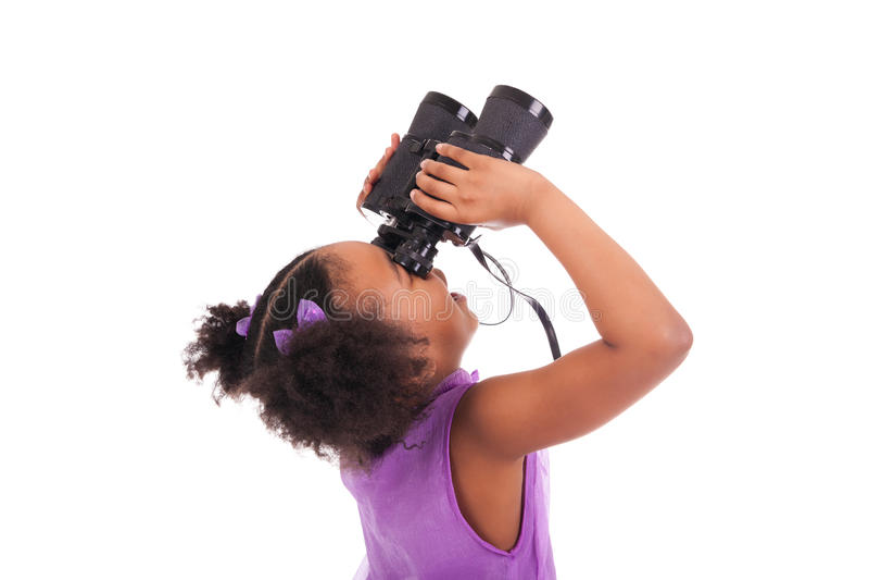 Petite fille africaine regardant par des jumelles d'isolement sur un ove photographie stock