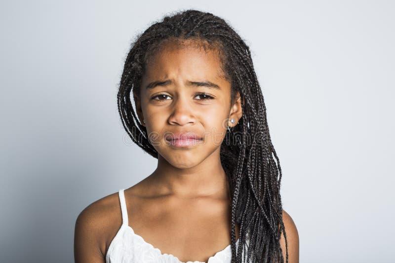 Petite fille africaine triste adorable sur le fond de gris de studio images stock