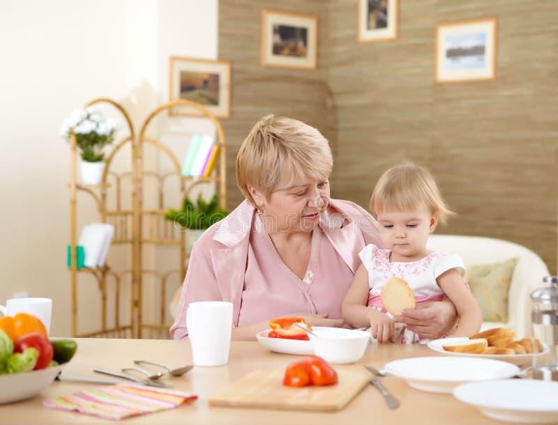 Petite-fille alimentante de grand-mère à la maison images stock