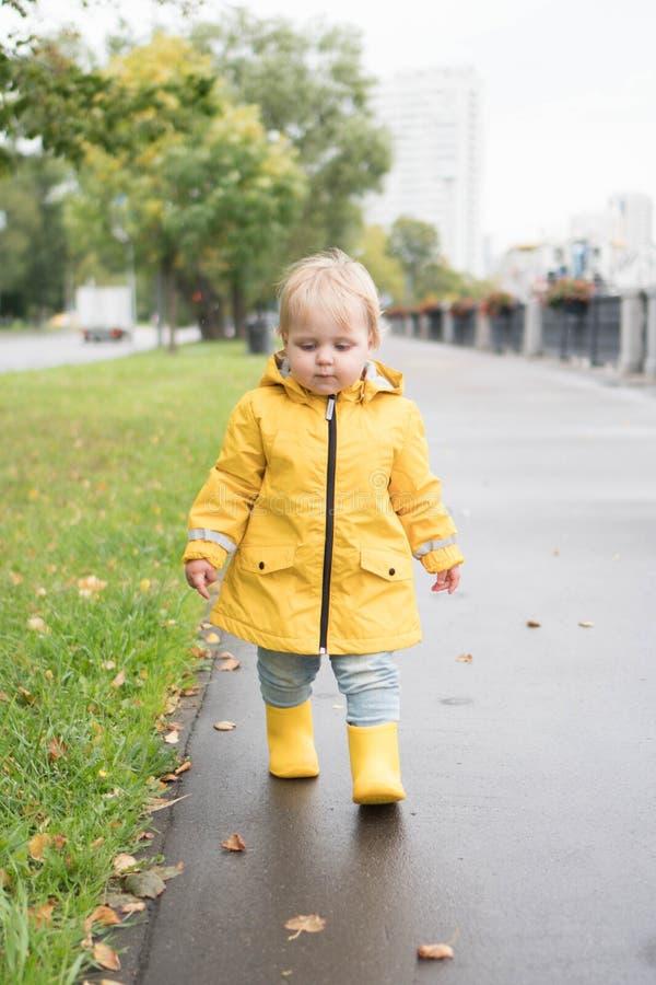 Petite fille amusante et calme de 2 ans en imperméable jaune marchant sur la route goudronnée par la pluie Une fille élégante qui images stock
