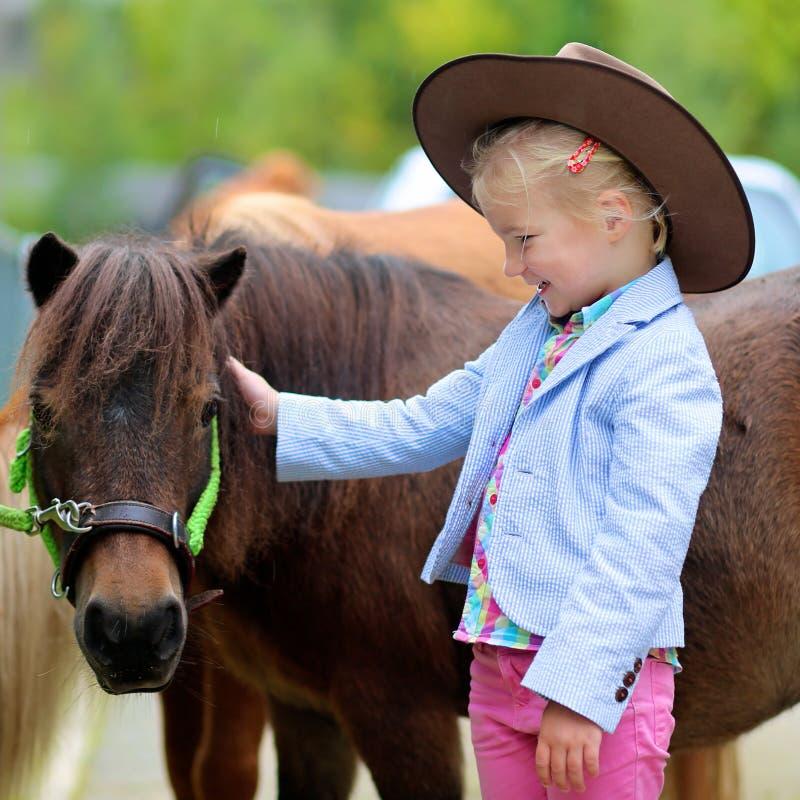 Petite fille appréciant son poney photos stock