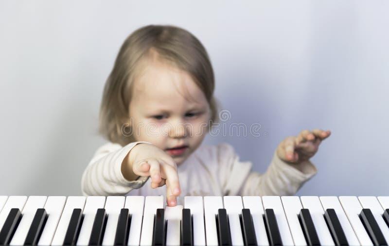 Petite fille apprenant à jouer le piano photo stock