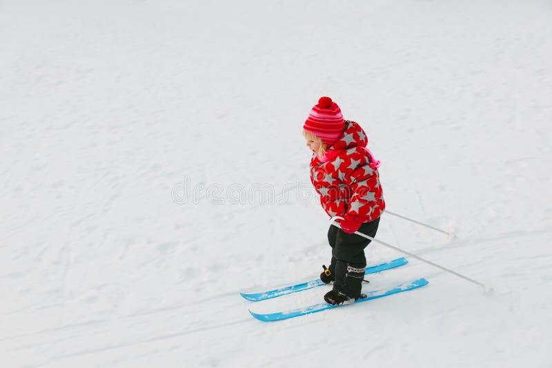 Petite fille apprenant à skier en hiver images stock