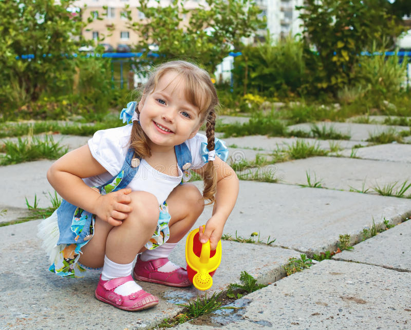 Petite fille arrosant l'herbe photographie stock