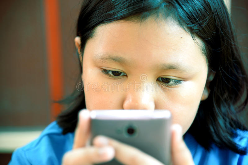 Petite fille asiatique à l'aide du smartphone photos libres de droits