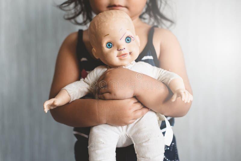 Petite fille asiatique étreignant sa poupée encrassée usée de favori photo stock