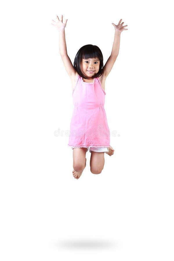 Petite fille asiatique adorable et heureuse sautant en air image stock