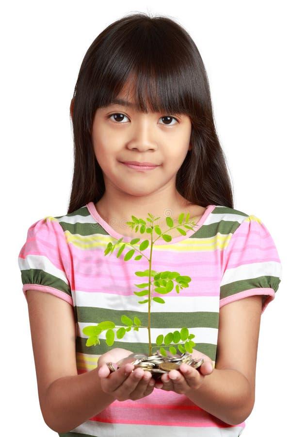 Petite fille asiatique avec la croissance de jeune plante des pièces de monnaie image libre de droits