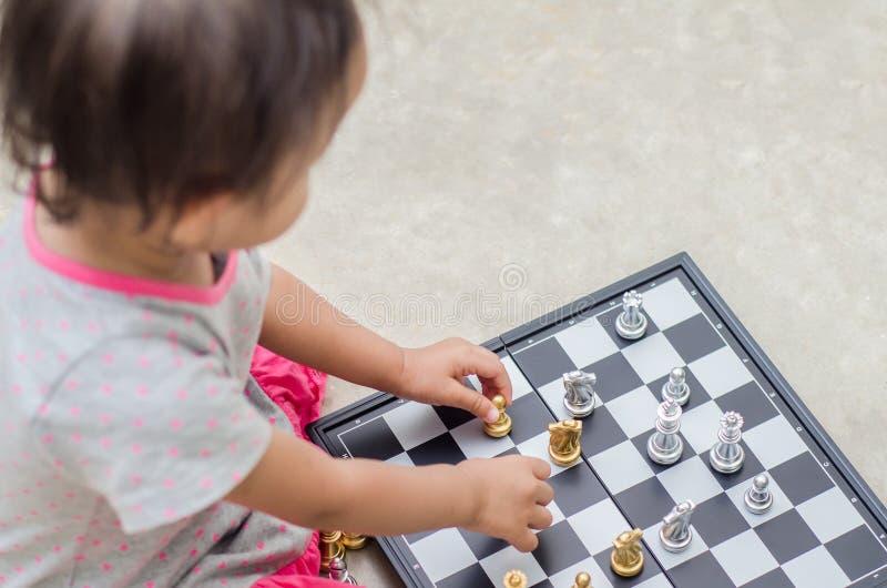 Petite fille asiatique avec le jeu d'échecs à la maison image libre de droits