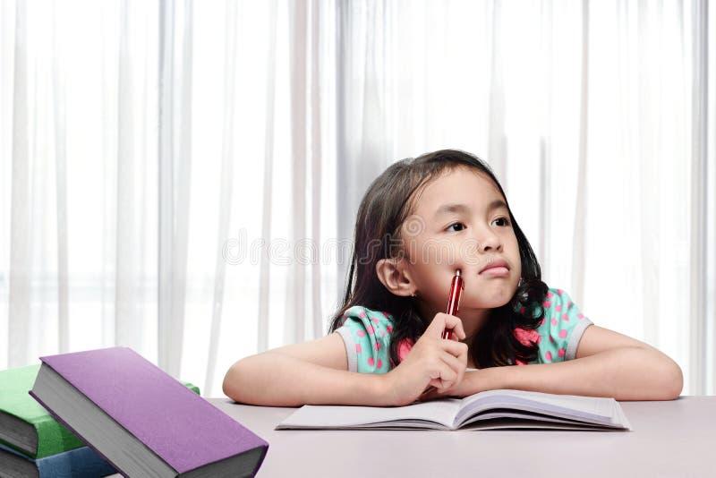Petite fille asiatique avec le livre et stylo pensant en faire le travail photo libre de droits