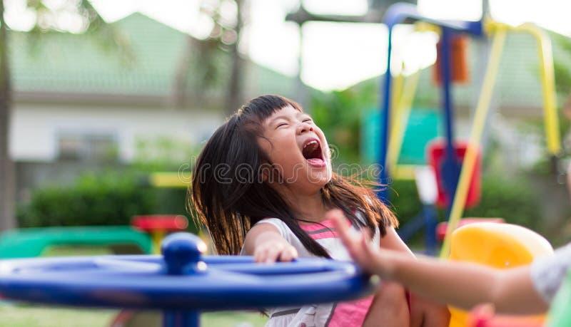 Petite fille asiatique ayant l'amusement jouant sur le carrousel photo stock