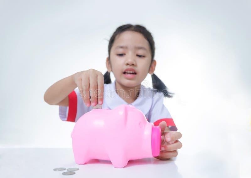 Petite fille asiatique dans l'uniforme thaïlandais d'étudiant mettant des pièces de monnaie à porcin photos libres de droits