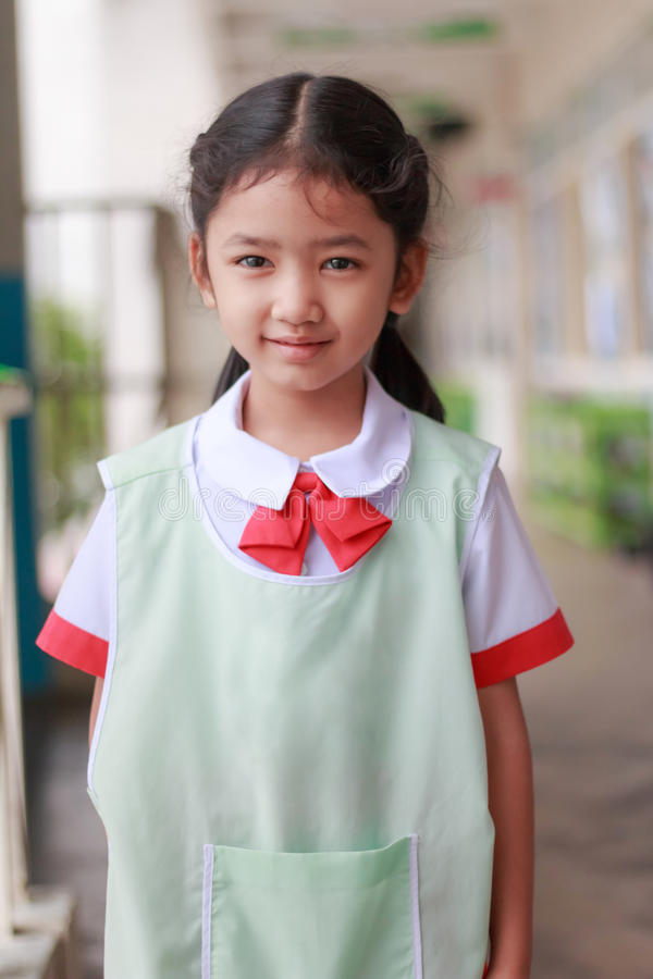 Petite fille asiatique dans le jardin d'enfants dans le smilin thaïlandais d'uniforme d'étudiant photos stock