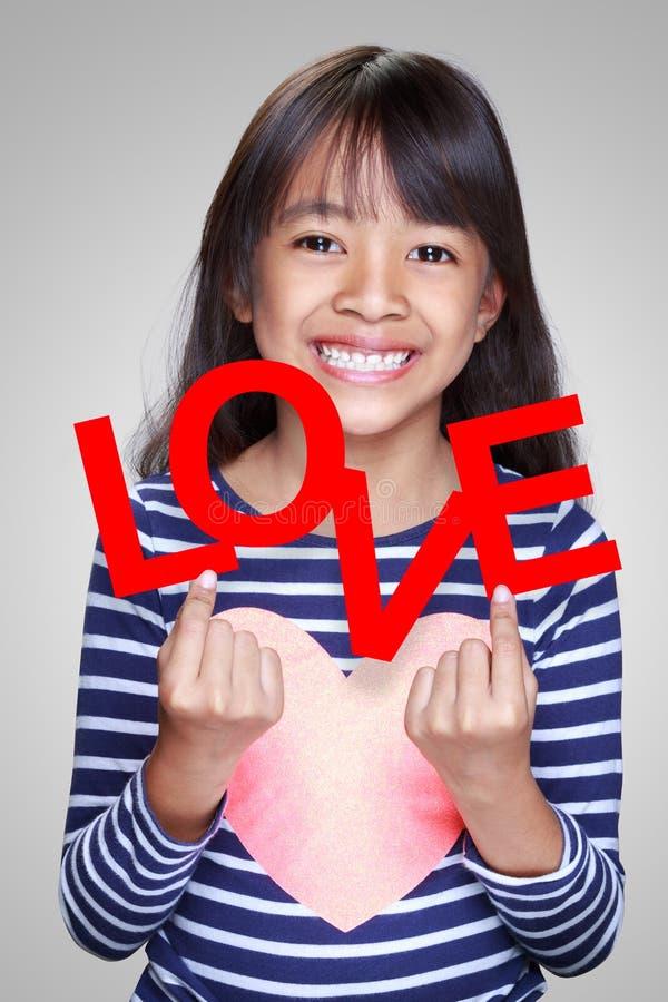 Petite fille asiatique de plan rapproché tenant le mot rouge photographie stock