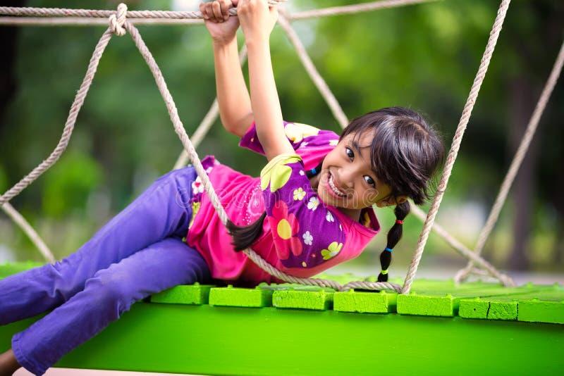 Petite fille asiatique heureuse sur le terrain de jeu image libre de droits