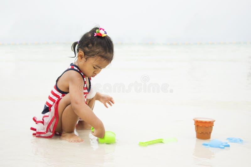 Petite fille asiatique jouant dans le sable photographie stock libre de droits