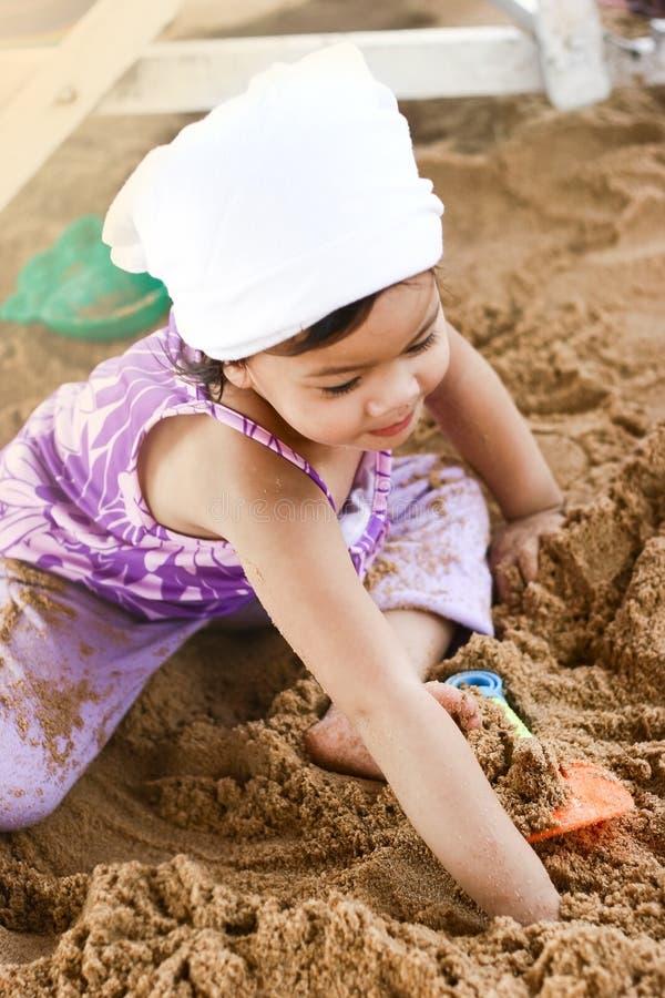Petite fille asiatique jouant sur le sable image libre de droits