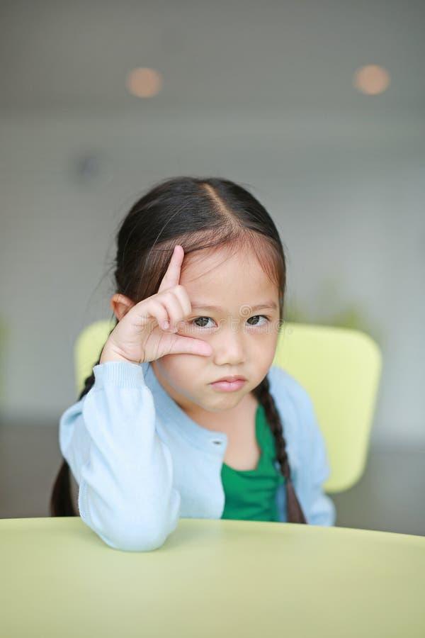 Petite fille asiatique mignonne d'enfant s'étendant sur la table d'enfants avec regarder la caméra photos stock