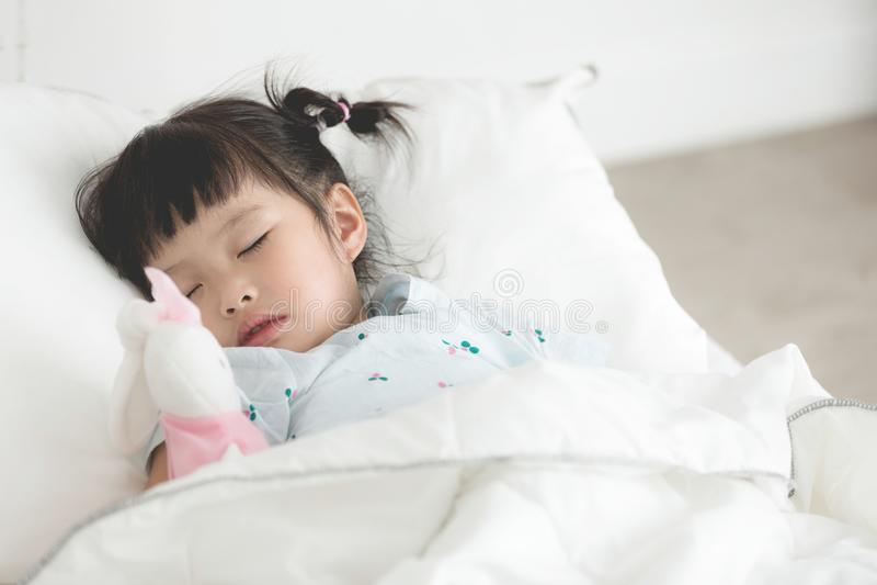 Petite fille asiatique mignonne dormant avec la poupée dans le lit image libre de droits