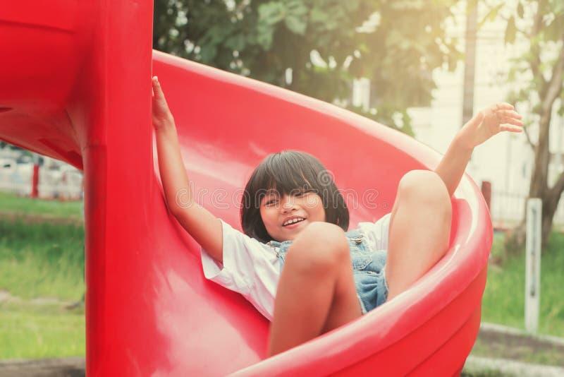 Petite fille asiatique mignonne jouant le glisseur dans le terrain de jeu images libres de droits