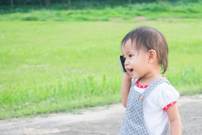 Petite fille asiatique parlant au téléphone intelligent en parc images stock