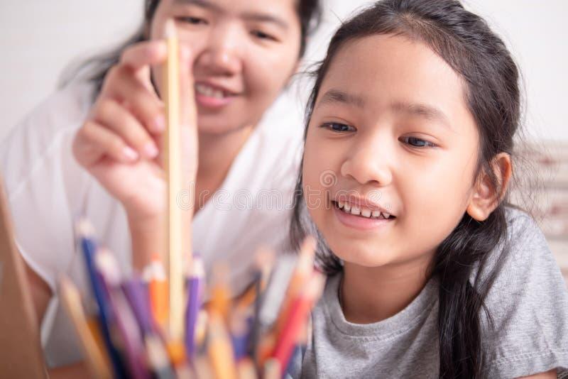 Petite fille asiatique sélectionnant un crayon de couleur d'or photos stock
