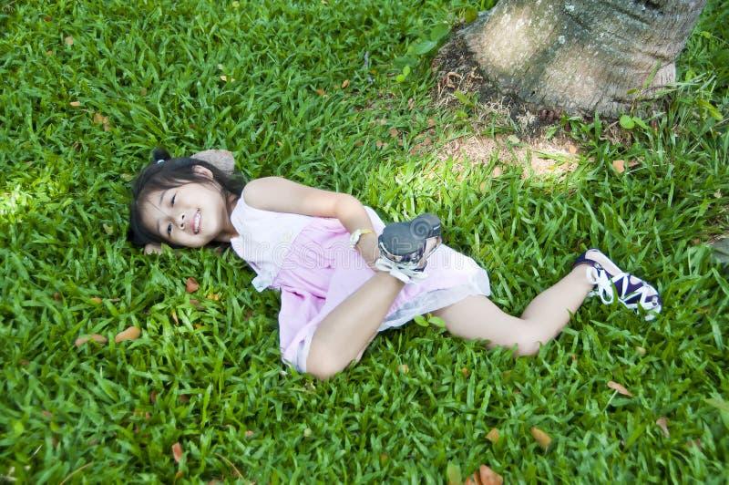Petite fille asiatique se trouvant sur l'herbe verte. image libre de droits