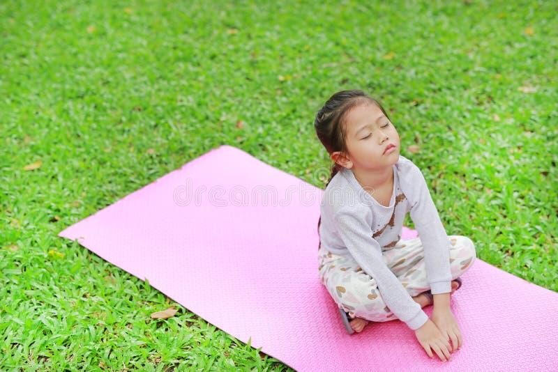 Petite fille asiatique somnolente d'enfant s'asseyant sur le matelas rose dans la pelouse d'herbe verte Enfant fermé de yeux exté photos libres de droits