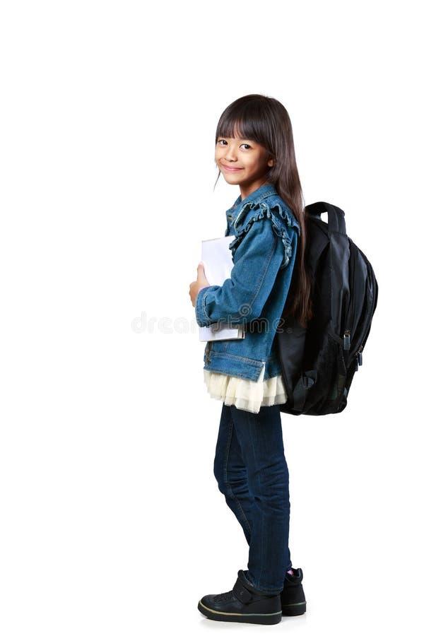 Petite fille asiatique tenant et tenant des livres image stock